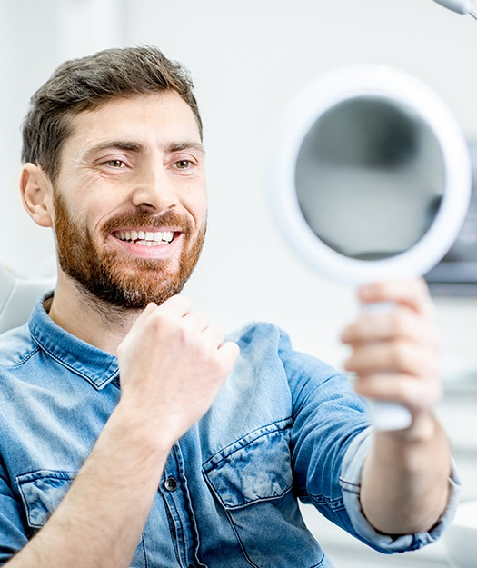 Man looking at smile in mirror after dental treatment