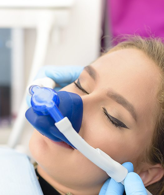 Woman resting with nitrous oxide sedation dentistry mask in place