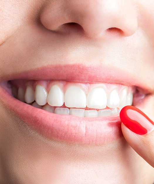 Patient pointing to smile after scaling and root planing treatment