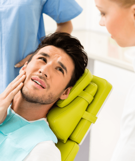 Man at emergency dental visit holding cheek in pain