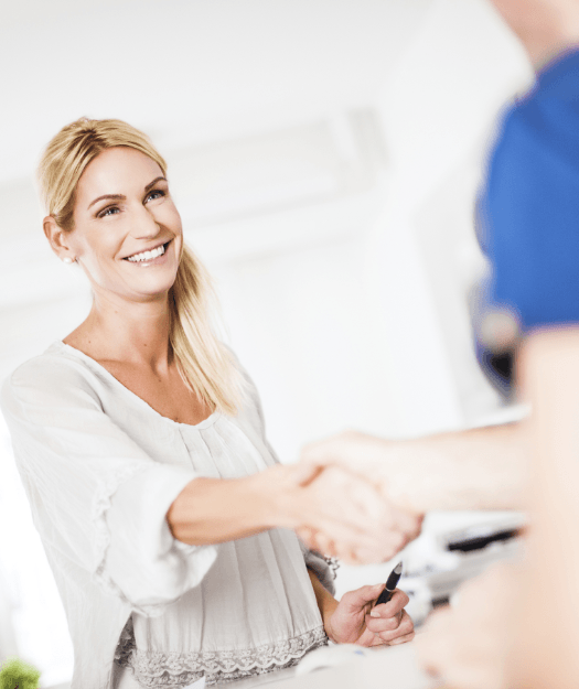 Patient shaking hands with dental team member at reception desk