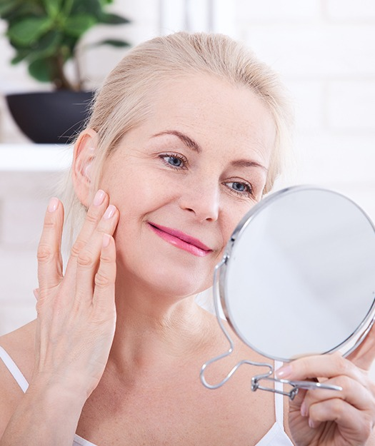 Older woman looking at flawless skin after Botox treatment