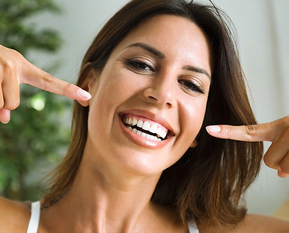 Woman pointing to flawless smile thanks to preventive dentistry