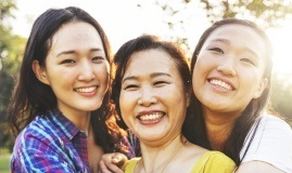 Three women sharing healthy smiles after preventive dentistry checkup