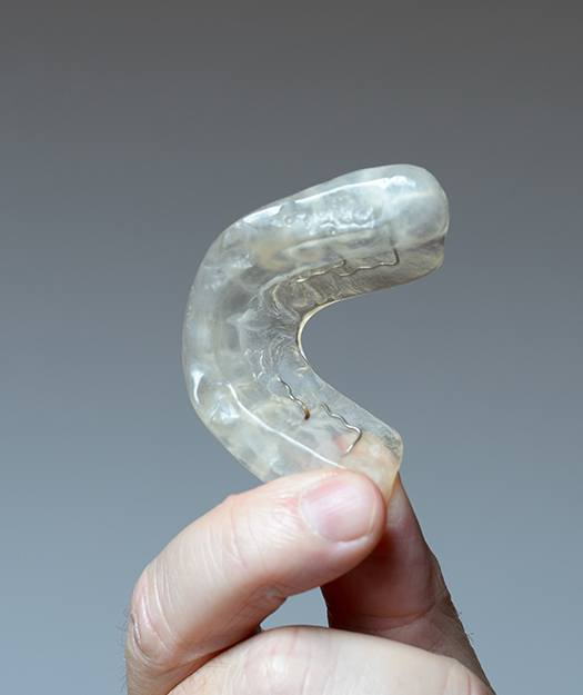 Hand holding up an oral appliance